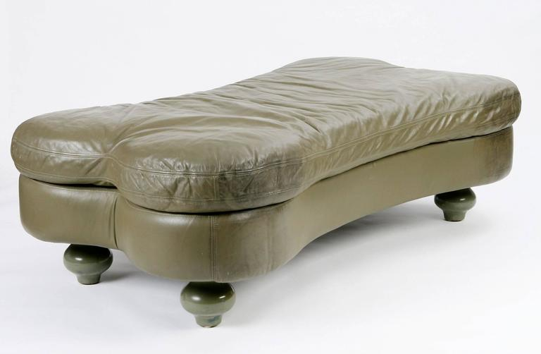 Bone-shaped daybed in olive leather raised on four lacquered turnip feet.