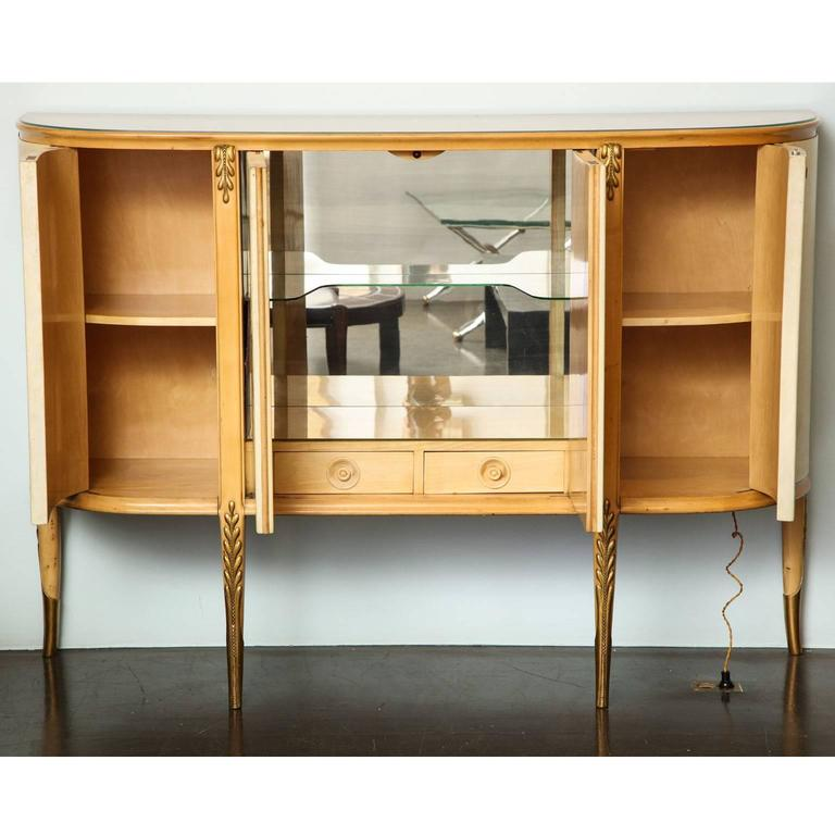 Giovanni Gariboldi (1908-1971) Illuminated bar cabinet in sycamore, pearwood and carved giltwood, with fruitwood inlaid parchment doors. The central compartment opening to reveal one glass shelf and two sycamore drawers the sides open to reveal one