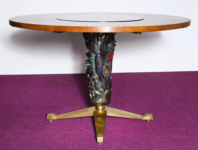 Circular center or dining table by Melchiorre Bega for Altamira. Rare and extraordinary table featuring a pedestal base with a large ceramic sculpture by Pietro Melandri and inset glass panel with reverse-gold-relief by Angelo Bragalini. Walnut top