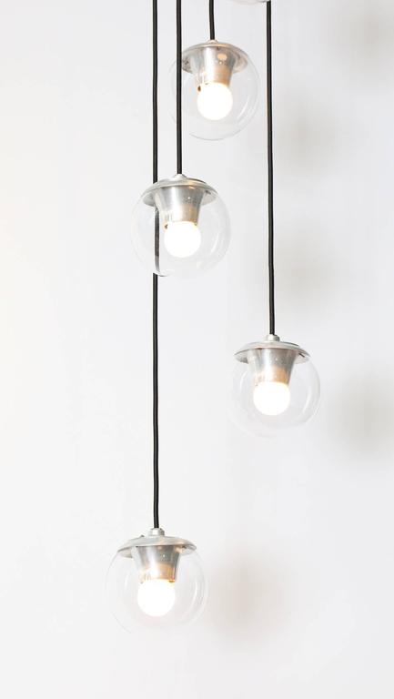 Gino Sarfatti for Arteluce five-light hanging fixture #2095. Cascading light with five glass globes hanging at different heights. Each orb contains 1 Edison sized socket. A beautiful and rare Sarfatti design.