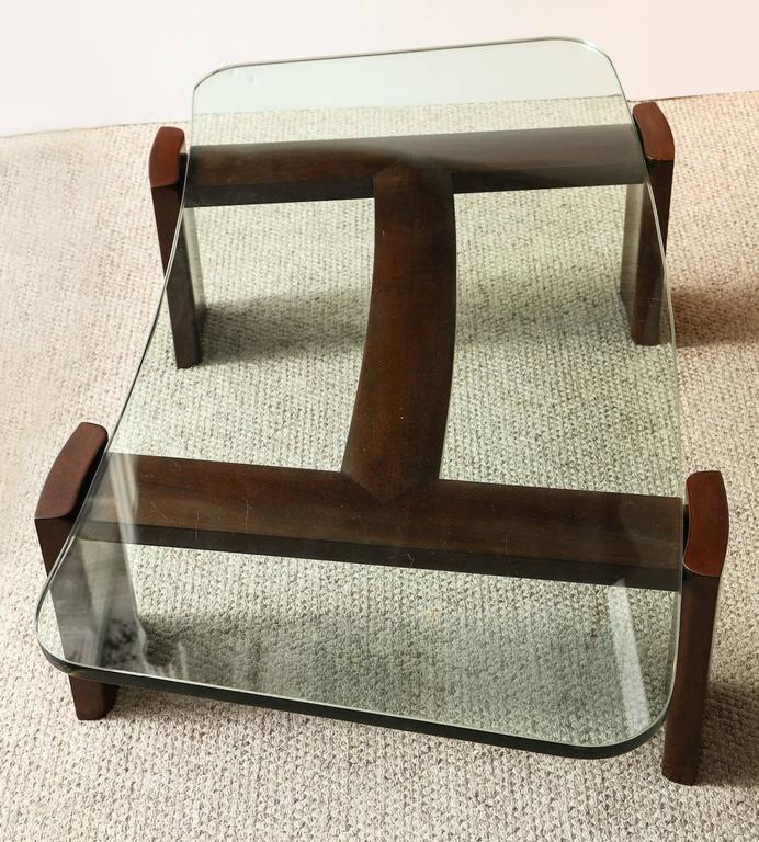 "Paul Laszlo custom table of dark stained mahogany. Shaped elements joined to form and abstract ""H"" shape. Thick, curved glass top insets into the structure. Paul Laszlo metal label affixed to underside of table."