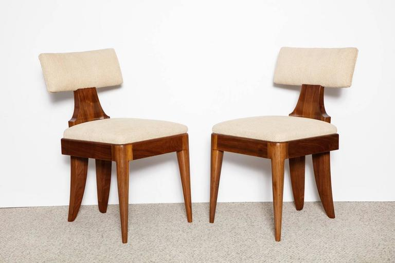 Rare pair of side chairs by Andrew Szoeke. Elegant sculptural forms in teak with upholstered seats and backs. Each chair is signed with a metal label. These chairs rarely appear on the market and are one of Szoeke's strongest designs.