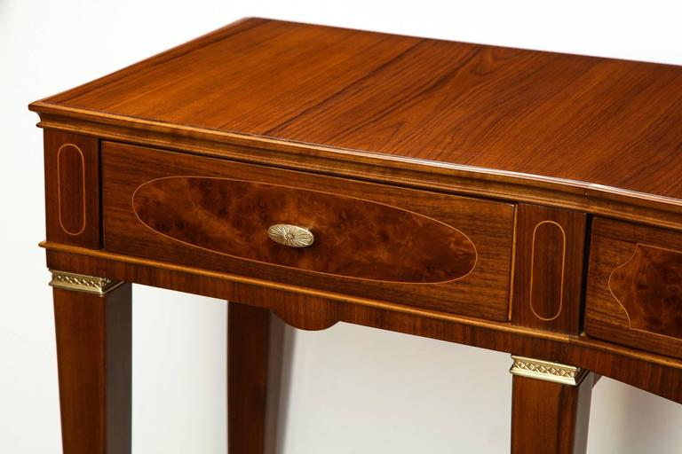 Three-drawer console table by Paolo Buffa. Extraordinary table of teak, mahogany and burled wood with light wood inlays. Bowed center front section, three drawers with cast brass pulls and brass mounts on legs. An excellent example of the cabinet