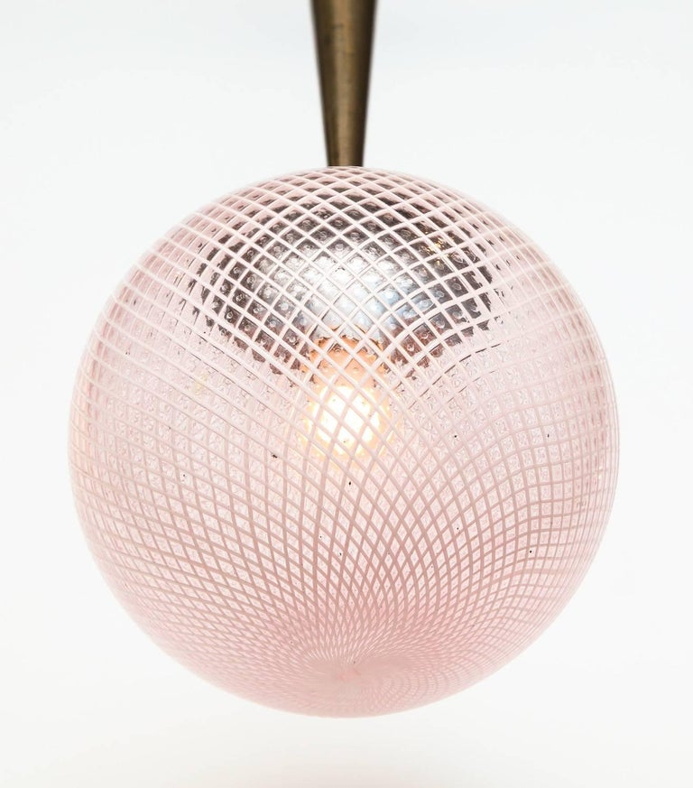 Rare Globe Pendant by Carlo Scarpa for Venini. Beautiful filigrana glass globe with a pale pink hue. Oxidized brass mounts and cone, and one standard sized socket. The chain was added later and can be removed to decrease the overall drop.