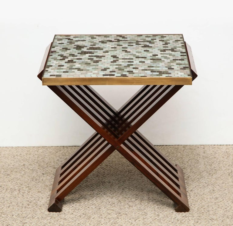 Side table #5425, by Edward Wormley for Dunbar. Beautiful interlocking and folding wood base with highly figured graining. Brass-rimmed top with inset Murano glass tiles of pale blue, green, brown and white. Green Dunbar tag attached to underside