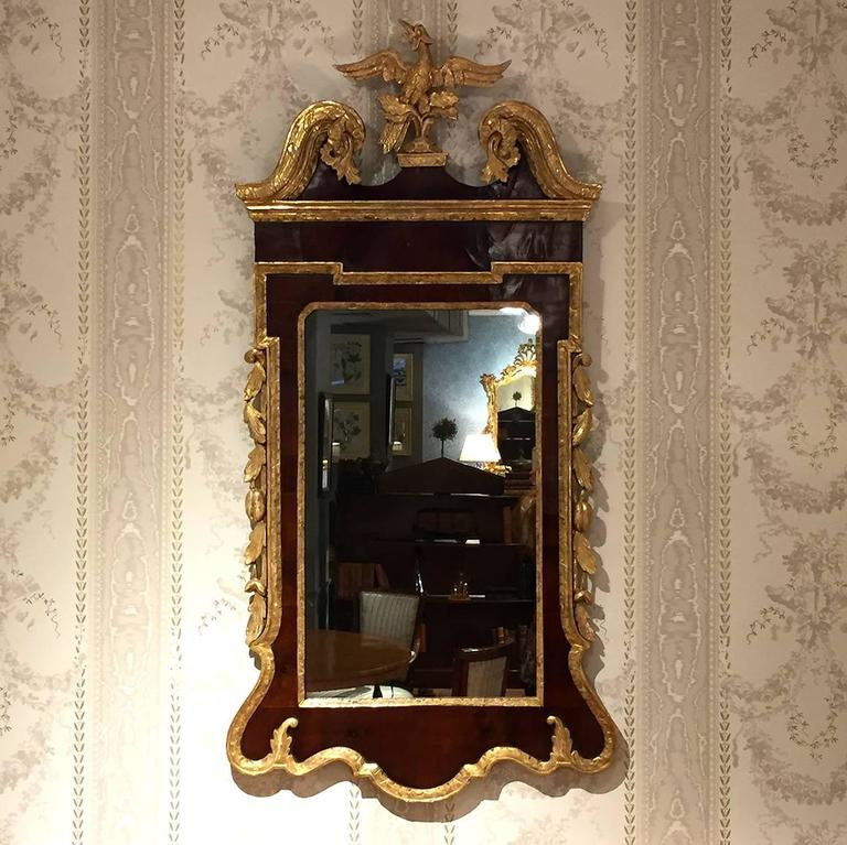 This George II mahogany and parcel gilt mirror is topped by a swan's neck pediment which is centered by a gilt ho-ho bird. The sides are ornamented with gilt fruiting vinery, flanking a rectangular mirror glass, and above a shaped apron.