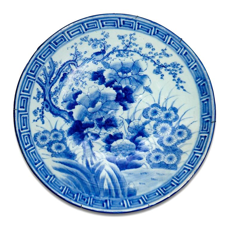 Each of these Meiji-period porcelain chargers is ornamented in cobalt blue with a floral design and a geometric border.