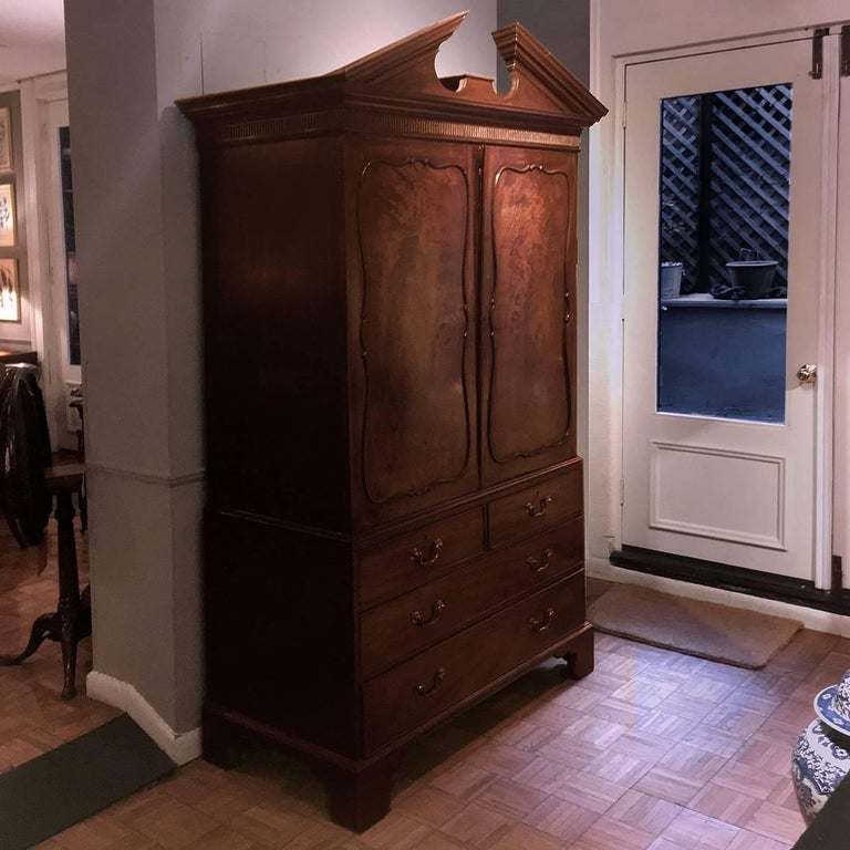 This early 19th century George III linen cupboard features a broken pediment and a fluted frieze, with two paneled doors opening to three sliding-tray shelves, above two short and two long drawers. With original brass pull handles and keyhole