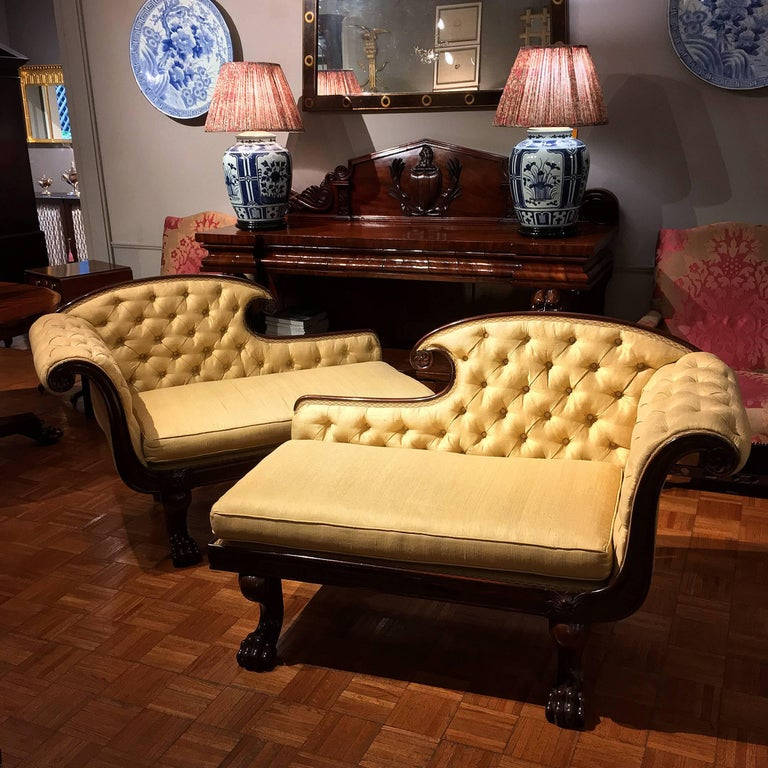 This pair of early 19th-century William IV chaises longues or chaise lounges is distinguished by their unusually small size. They are ornamented with carved rosettes, and with lion's paw feet in the front and turned legs in the back. Each with