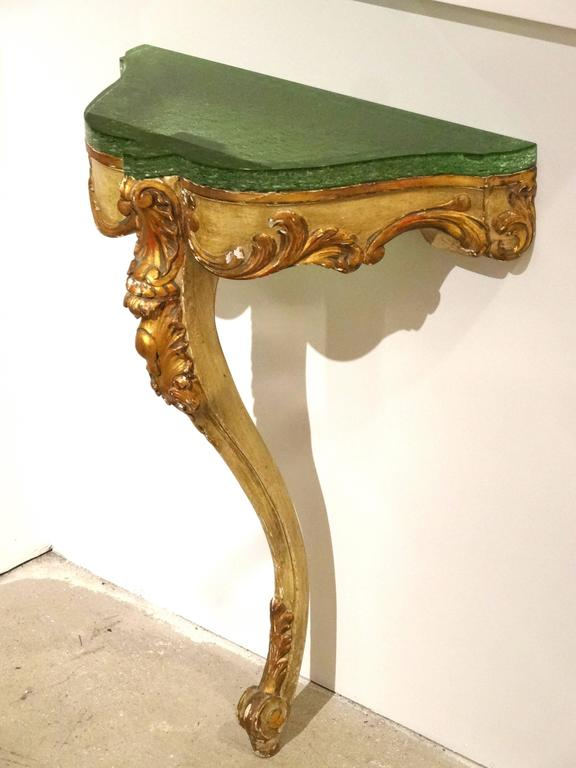 A beautifully aged painted and gilded console with a new modern custom Lucite top. Nicely carved details which are highlighted by the gilding. The modern colored Lucite slab add a bit of modern complimenting the classic form.