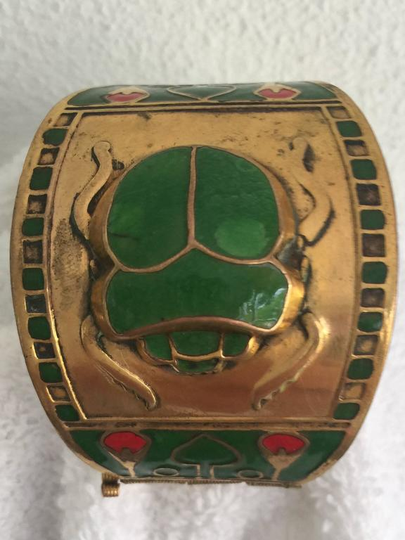 An Egyptian revival style cuff in enamel and brass. Beautifully designed with a scarab and lotus motif.  The design is highlighted by the vibrant and complimentary colors. Hinged with a pin closure. Beautiful piece of jewlery. Seems to have an