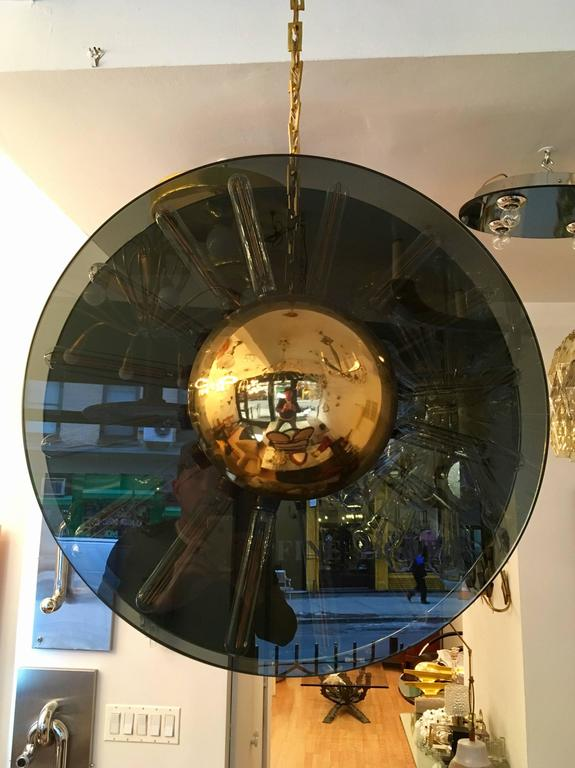 A 1980s Italian pendant of composed of two large half inch thick smoked glass plates and polished brass hemispheres. Newly rewired. Very unusual and unique.