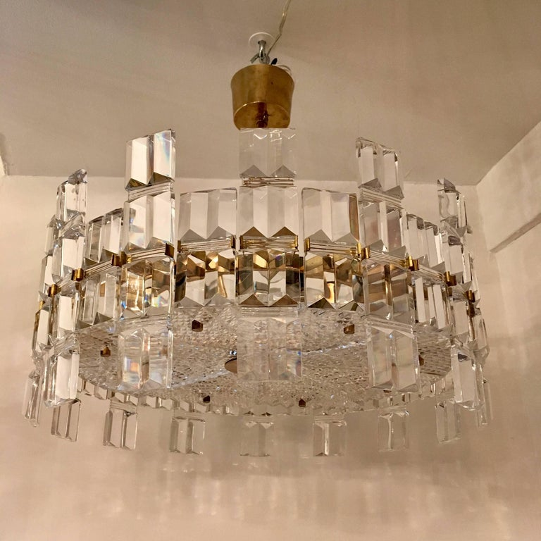 A beautiful luxurious thick crystal and polished brass chandelier by the famed Swedish maker, Orrefors. Rare. Eight light sources. Newly Rewired. Located in our New York City Chelsea location.