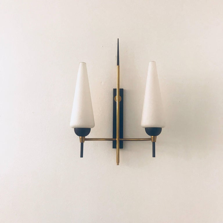A set of two 1960s French wall lights composed of golden brass and black enamel frames holding white cone glass shades. Newly rewired with matching backplates. 120 Watts each . The sconces are by the French lighting company, Lunel.