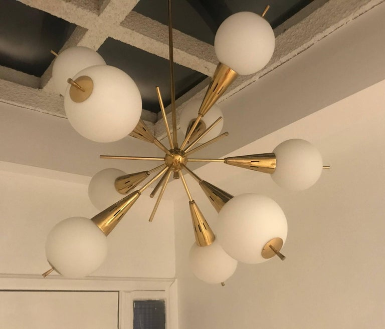 An original Italian pendant composed of a golden ages brass body with jutting rods and white glass globes forming an unusual Sputnik style. Newly rewired.Located in our New York City Chelsea location.