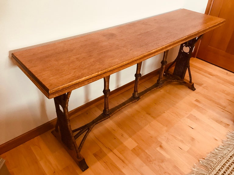 A custom 1960s oak top and rattan base large console table with oak claw carved feet. Made for an Astoria, Oregon Hotel. Great original patina.