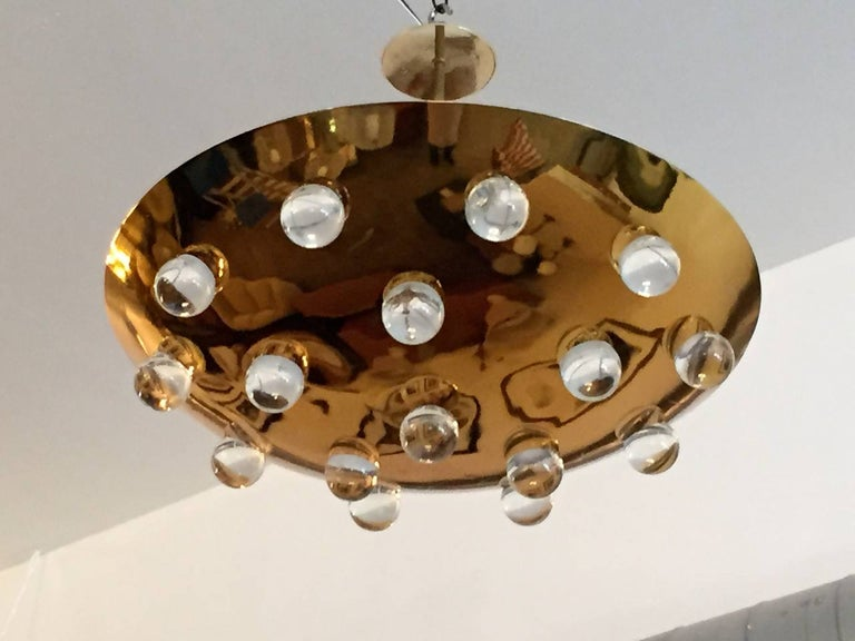 A wonderful pair of 1960s French gold-plated brass round disc fixture with 16 solid glass orbs. Five-light sources which emit light downward through the glass as well as up toward the ceiling. The ceiling pole can be lengthened or shortened. Rewired