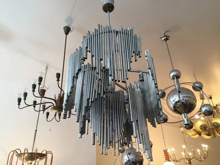 A 1970s high style Italian sculptural chrome chandelier. The chandelier has ten lights sources and is composed of steel pipes in varying length which freely swing on the chrome frame. Rewired. Rare.