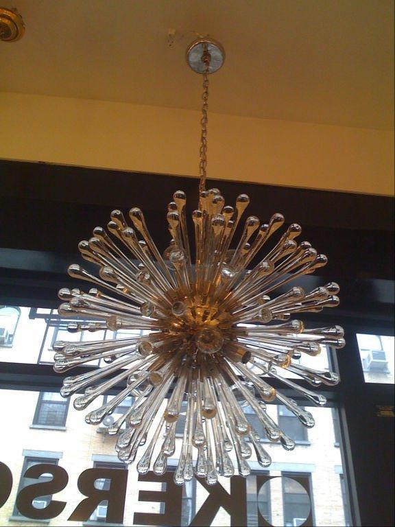 A 1960s Italian glass and nickel chandelier. The polished nickel frame has nine lights and 150 teardrop glass elements radiating from the center. Matching canopy.