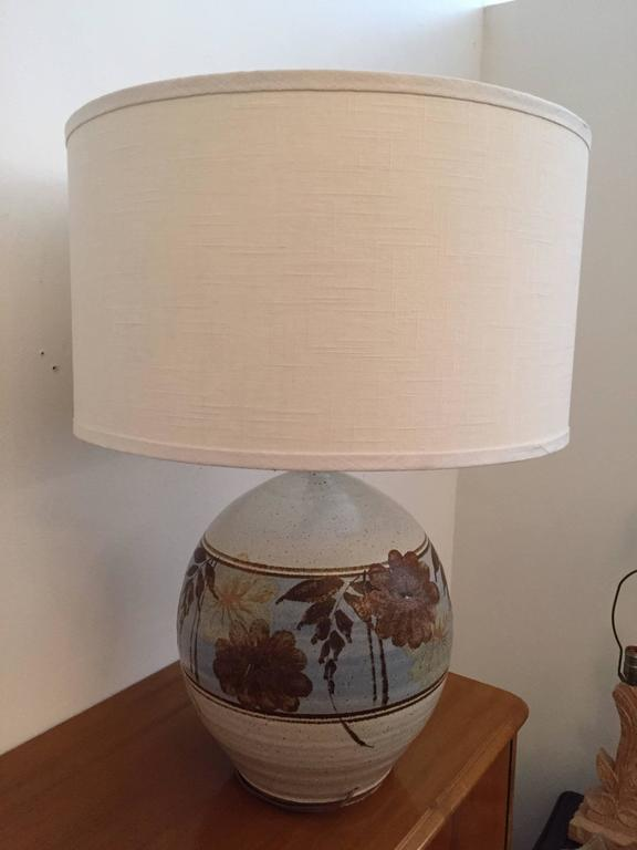 An original pair of 1970s, California, Mid-Century Modern art pottery stoneware table lamps. The ball shaped ceramic lamps are done in muted colors of beige, brown, and blue. Newly rewired. Made by California Ceramic Company.