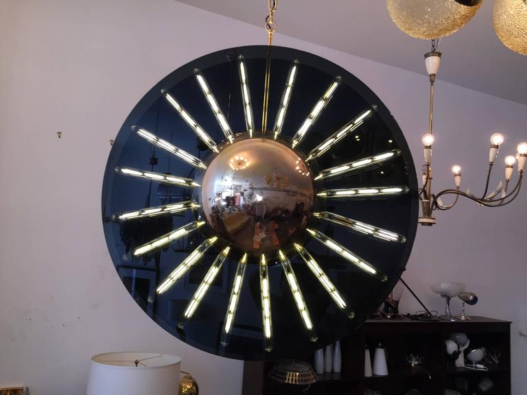 """A very large, luxurious, artist made chandelier composed of two 40"""" dark smoked glass elements and two polished brass half orbs. 20 light sources which make a sun pattern when lit. The 20 LED tube bulbs are only 6watt each but are equivalent to"""