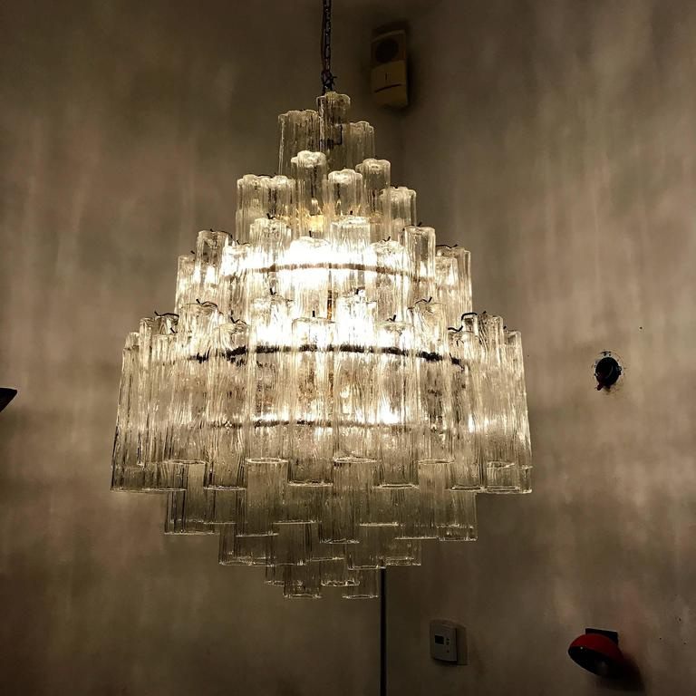 """A beautiful 1970s Murano glass chandelier composed of an polished brass frame and driven tiers of """"tronchi"""" glass tubes. Newly rewired."""