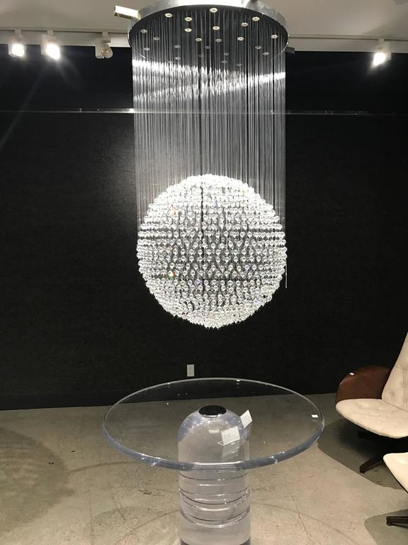 A rare limited edition Tom Dixon designed chandelier for Swarovski for the Crystal Palace collection. The chandelier is composed of a polished chrome fixture with hundreds of large Swarovski crystals hanging from clear threads to form one large