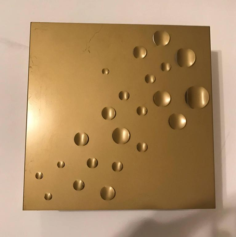 """A great 1960s Space Age """"rain drops"""" wall light by Dutch maker, RAAK . The square frame is composed of a matte gold steel enameled frame with perforated decorative indents to emit light as well as an open bottom and top. Two standard"""