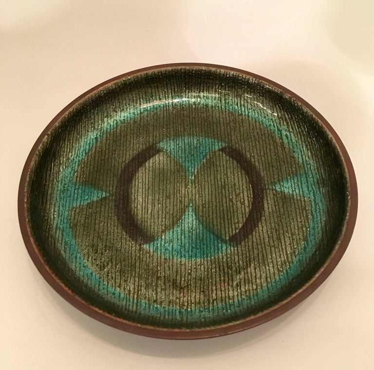 A 1960s handmade enamel over copper with an abstract design in colors of black, and olive and teal green. Signed.
