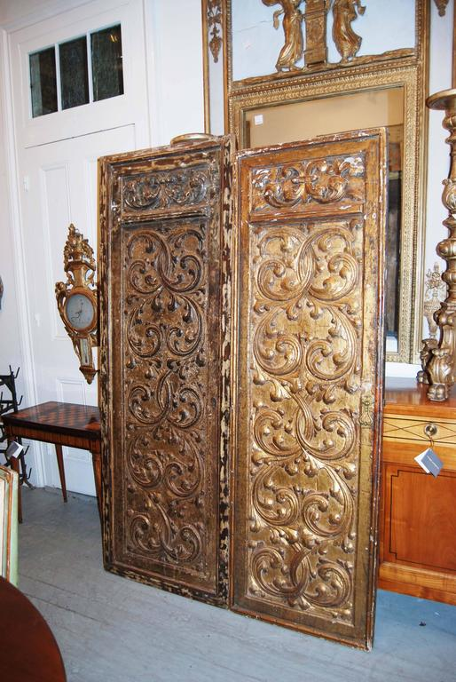 Two beautifully carved and gilded doors. The patterns appear to be the same but the size differs. Largest door Measures: 82 high 28.75 wide 2 depth.