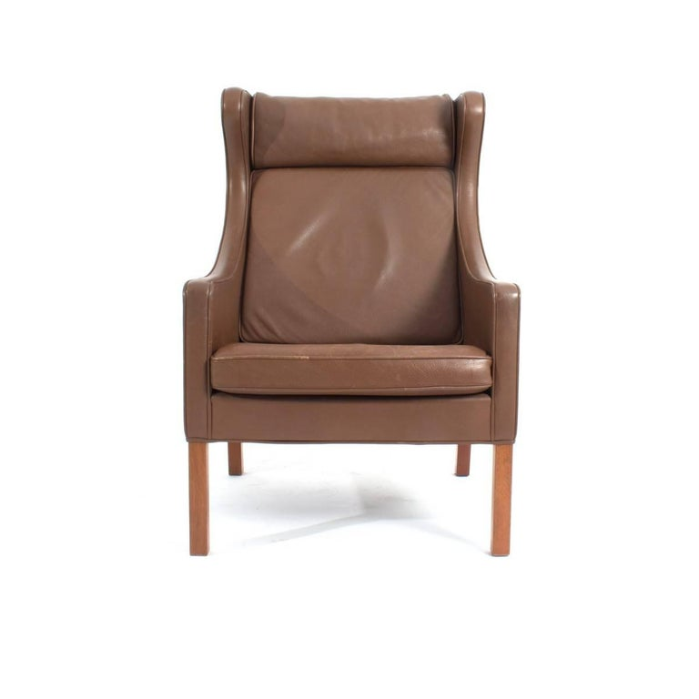 Borge Mogensen brown leather wingback lounge or easy chair; model 2204, and ottoman model 2202. Produced by Fredericia Stolefabrik in Denmark.  He was one of the most important among a generation of furniture designers who made the concept of