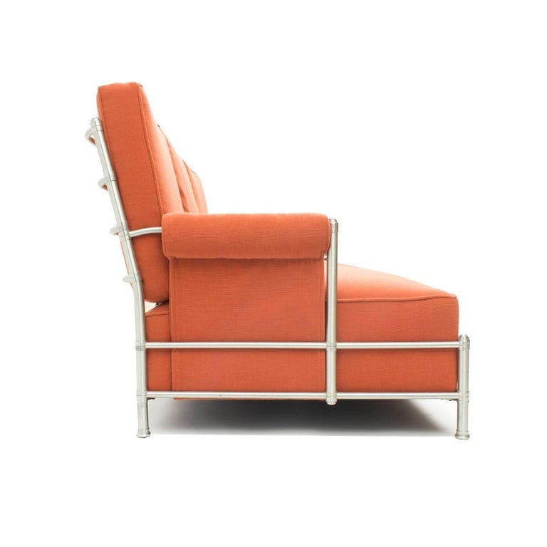 Rare Warren McArthur Art Deco three-seat sofa, circa 1930s with a satin finished aluminium frame with decorative joints and capped legs. The upholstery is in a tangerine woven fabric and appears in very good condition. It has the original label