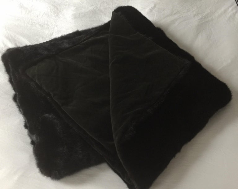 A custom mink fur throw blanket. Lined in olive green cotton velvet. Dark brown. Made in USA, circa 2010. Measures: 84 inches x 48 inches.