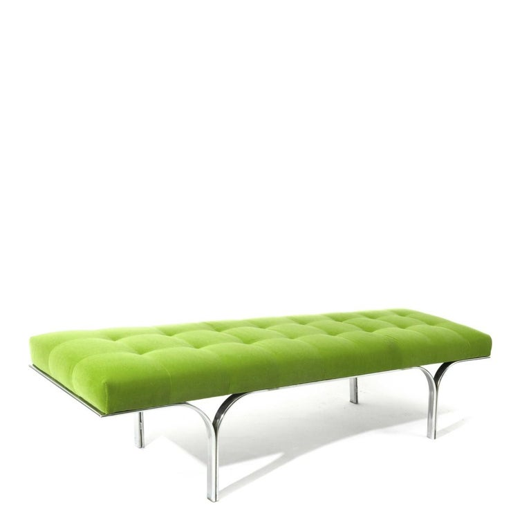 A vintage bench with apple green velvet tufted upholstery and chrome double arched base, USA, circa 1960.