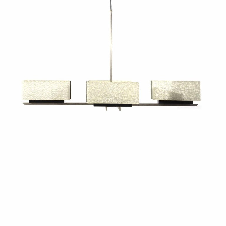 A four-arm, brushed metal hanging light fixture with rectangular-shaped Perspex shades. France, circa 1960.   Dimensions: 43 inches L x 18 inches W × 24 inches H (total drop height with stem).