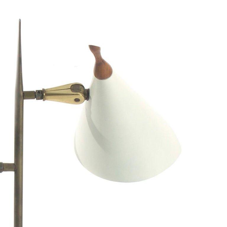 A brass, white metal and wood two-arm desk lamp featuring cone shaped shades, a square base and walnut finial. Likely made by Lightolier. USA, circa 1970.  Rewired; takes two standard US bulbs, 60 watts max each.   Dimensions: 17.5 inches L × 6