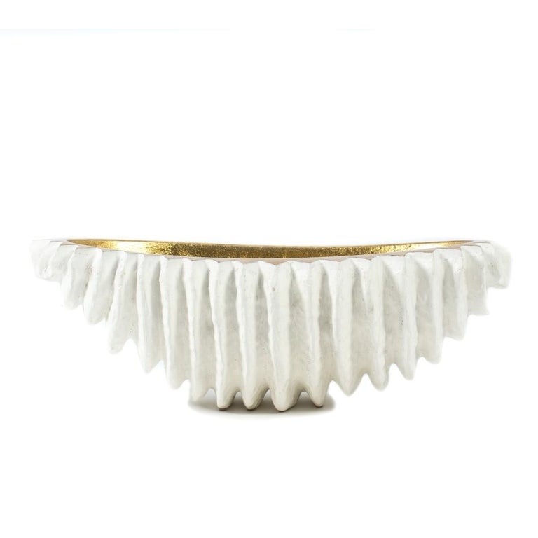 A dramatic, large scale white and gold centerpiece bowl by Mecox Gardens, meanings 24 inches in length.  Features a sculpture; seashell-like exterior and contrasting gilt interior.  Metal.   Dimensions: 24 inches L x 13 inches D × 8 inches H