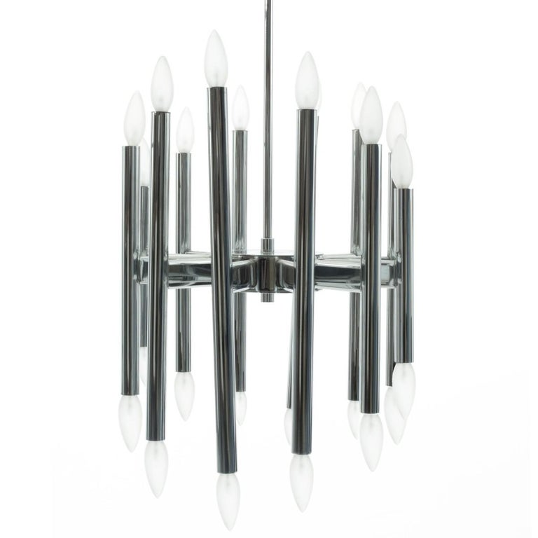 A 12-arm chandelier in polished chrome by Gaetano Sciolari for Lightolier, USA, circa 1950.  Wired for US; in very good condition. Takes 24 candelabra base bulbs, 40 watts max each. Includes hanging matching hanging stem. Totla drop height is 29