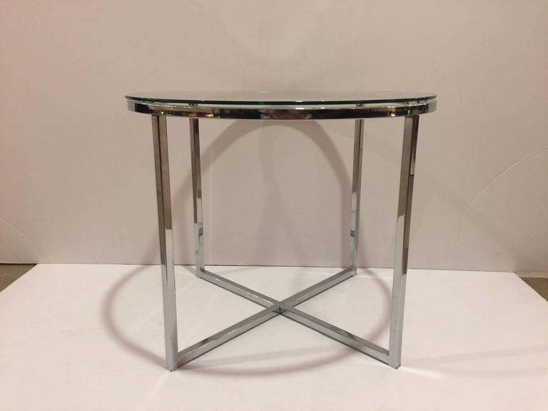 A polished chrome round end table with round glass top and cross-leg base attributed to Milo Baughman. USA , circa 1970. Unsigned. Measures 21.5 inches wide by 17 inches tall.