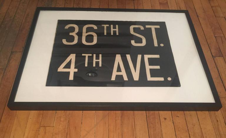 A segment of a vintage New York destination sign in black canvas with white text, circa 1950. Originally used on a subway (or bus) window sign on a roller mechanism. Newly mounted on an off-white linen matte, pleixglass and black wood