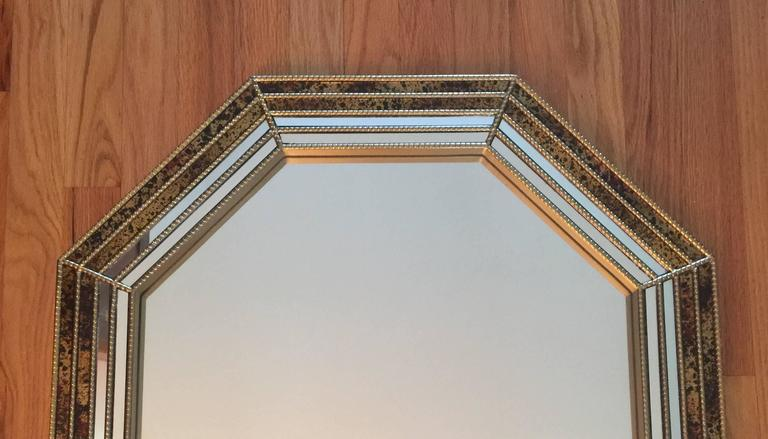 An octagonal-shaped wall mirror having a beaded brass frame with an oil drop inlaid decoration. Made by Chapman and evocative of the company's signature oil drop collection of table lamps. A substantial and beautifully made mirror. A series of rear