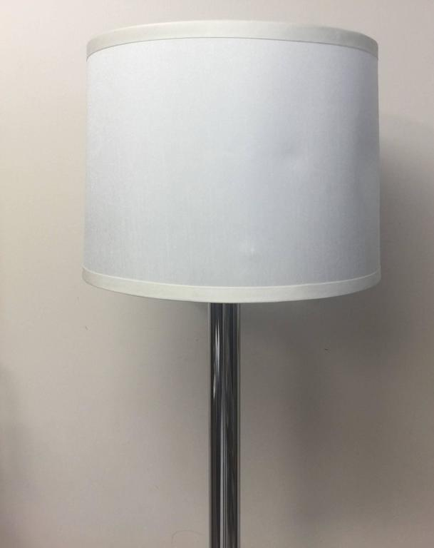 A polished chrome floor lamp with thick round base and cylindrical stem, USA, circa 1970. Unsigned.  Polished chrome floor lamp with round base. AMERICAN, circa 1960-1970.   Unmarked; similar in style to lamps by Sonneman, Nessen and