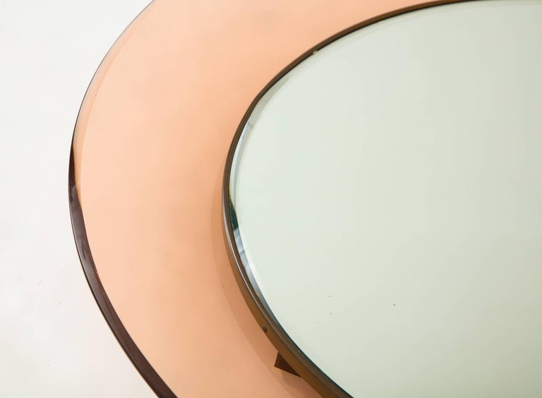 Round mirror by Max Ingrand for Fontana Arte, Italy 1966. Bevelled mirror set in a brass frame surrounded by a concave glass frame in pale rose. All original, original mirror date stamped 20 Mar 1968 on the reverse. Model number 1669, documented in