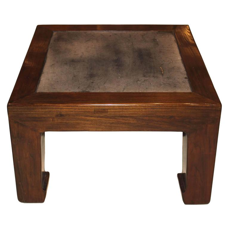 Chinese elm wood coffee table with vintage stone insert can be used in a contemporary home.