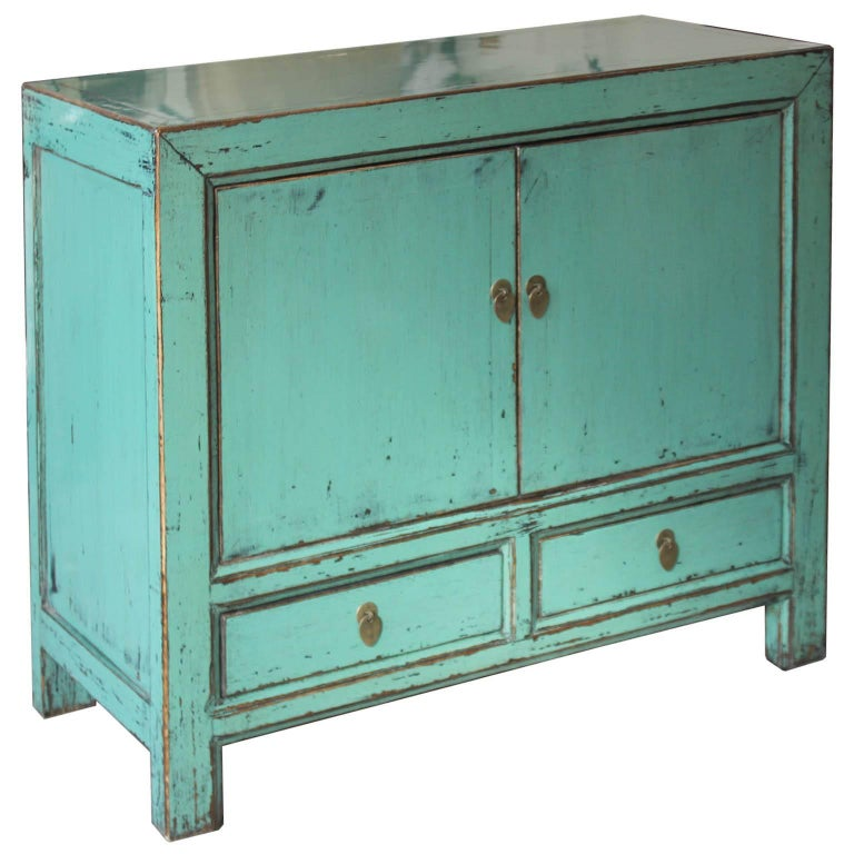 Elegant two-door turquoise lacquer sideboard with exposed woodedges.Place behind a sofa with accessories on top.