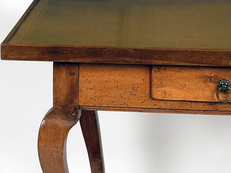 Italian leather topped walnut writing table with drawer, circa 1870. Standing on well carved cabriole legs with hoof feet. Nicely tooled and worn caramel leather top.