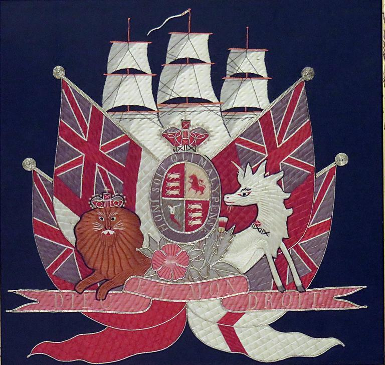 A handsome embroidered picture featuring a British ship under sail with assorted British commonwealth flags. A lion and unicorn frame a cartouche featuring heraldry and the motto of the Order of the Garter. We suspect the work of a talented child as