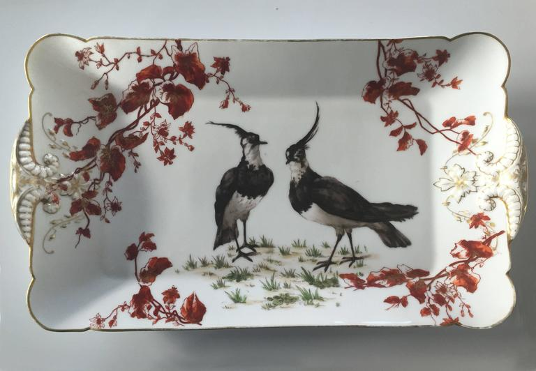 Gorgeous hand-painted platter by Charles Field Haviland, featuring two birds, surrounded by curling branches. The platter is marked by a manufacturer's stamp (CFH/GDM) on the bottom.