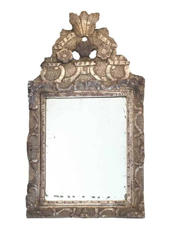 Beautiful small French Regence champagne leaf giltwood mirror with original mercury glass.The hand-carved front top and the frame, featuring three flowers. French Regence period, early 18th century, circa 1710.