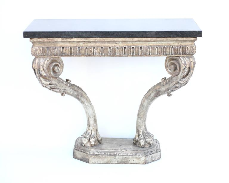 Mid-18th century beautiful period hand-carved George II console, the silver leafed apron with Classic arched fluted above stylized scrolling legs, the knees with carved acanthus culminating in lion paws on a stepped carved base with canted corners.